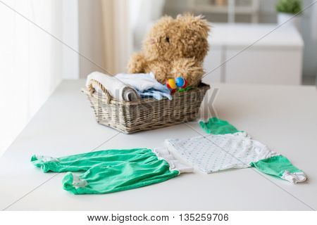 babyhood, motherhood, clothing and object concept - close up of baby clothes set and toys for newborn in basket at home