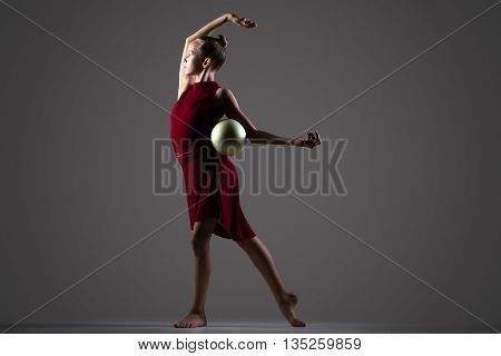 Beautiful cool young fit gymnast athlete woman in sportswear red dress working out doing rhythmic gymnastics exercise with white ball dancing full length studio dark background