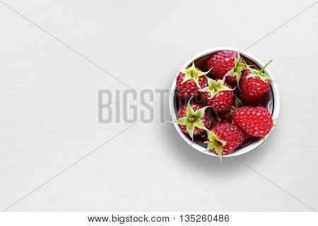 Ripe raspberry in bowl on white table