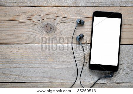 Smart phone with headphones on wooden background