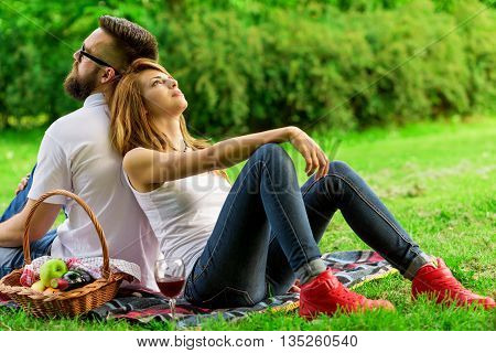 Couple sitting on a picnic blanket pensive and enjoying the peace and nature