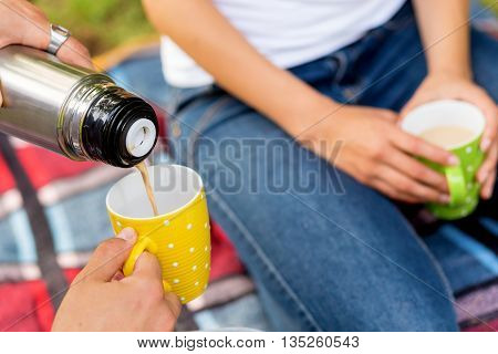 Young couple on a picnic in a park. Man pouring hot coffee from a thermos bottle. Focus is on the top of the thermos bottle and poured coffee