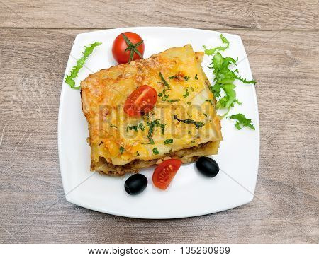 lasagna with meat tomatoes olives and greens on a plate. wood background - horizontal photo.