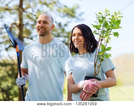 volunteering, charity, people and ecology concept - happy couple volunteers with tree seedlings and rake walking in park