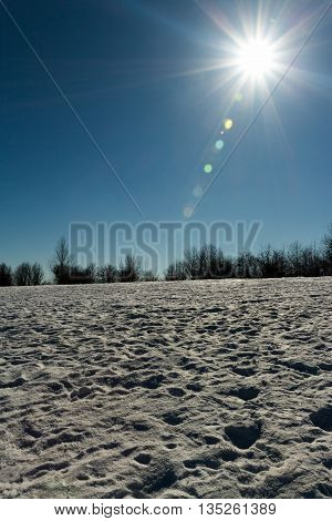 Photo of the midday sun on a snowy hill
