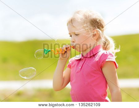summer, childhood, leisure and people concept - little girl blowing soap bubbles outdoors