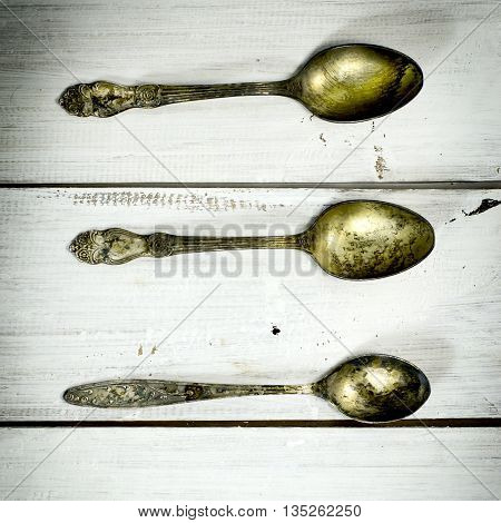 Three old spoons on a white wooden background. Top view