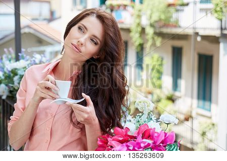 woman with cup of coffee to go against sunny italian house