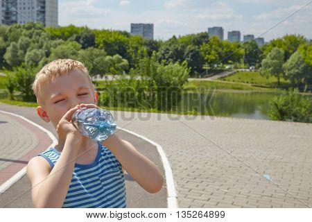 Child drinking pure water in the park