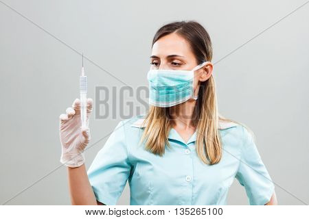 Portrait of nurse with protective mask holding injection.