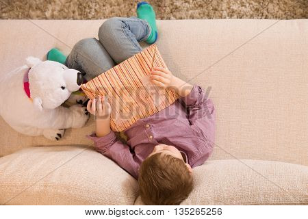 Kid boy sitting on a sofa and opening a present. Birthday gift. Child with a bear toy unwrapping his gift. Top view.