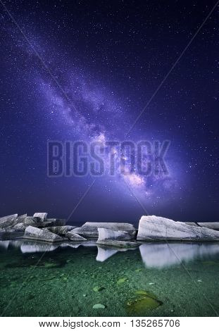 Night landscape with colorful Milky Way at the sea with stones. Starry sky. Space background