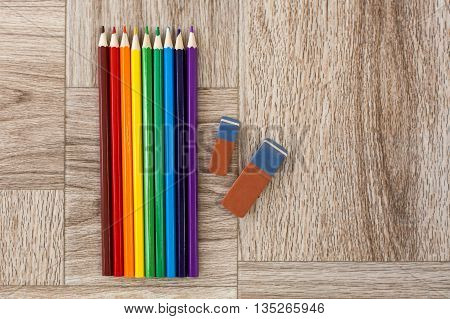 Lots Of Assorted Colors Pencils And Erasers On Wooden Background