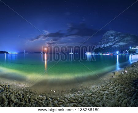 Beautiful night landscape at the seashore with yellow sand full moon mountains and lunar path. Moonrise. Vacations on the beach at the sea.