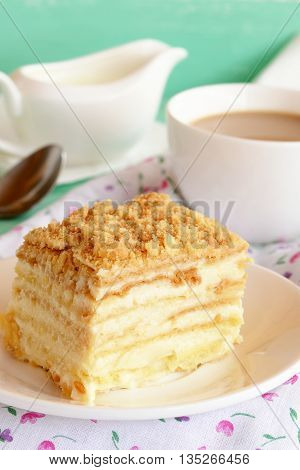 A piece of Napoleon cake. Cake of puff pastry with sweet cream on a plate. A cup of coffee milk. Spoon, fabric with floral pattern. Sweet fresh dessert. Home baking. Close-up