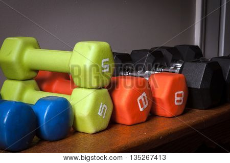 Colorful Weights On A Bench in Home Workout Room
