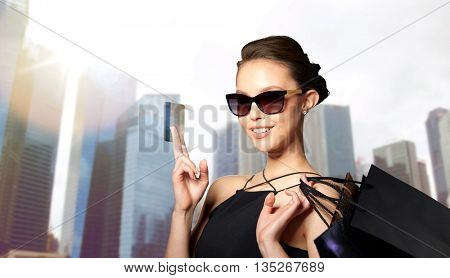 sale, finances, fashion, people and luxury concept - happy beautiful young woman in black sunglasses with credit card and shopping bags over city skyscrapers background