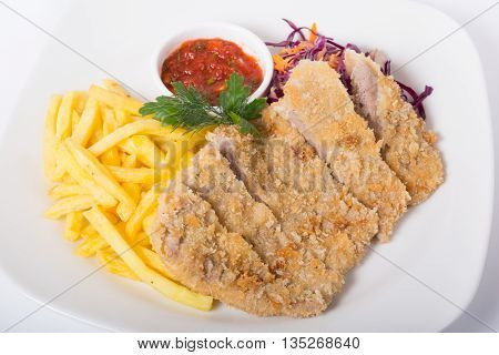 Fried meat with french fries and tomato sauce