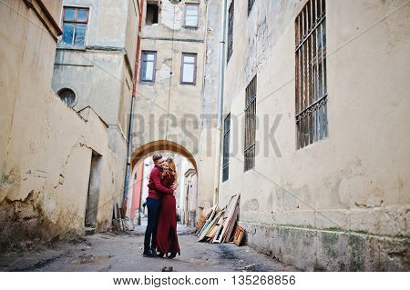 Young Beautiful Stylish Fashion Couple In A Red Dress In Love Story At The Old City, Running And Hav