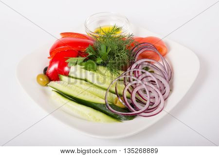 Fresh raw sliced vegetables and herbs on white plate
