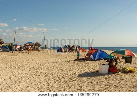 Moalboal.Cebu.Philippines - 06 april 2016: Philippine people with tents and ambrella getting rest and playing volleyball on the white bech