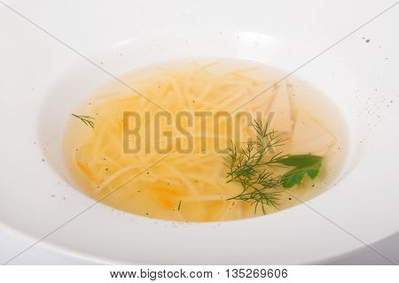 Chicken noodles soup served on a white plate