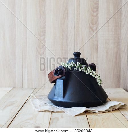 East Asian concept teapot on linen napkin in wooden interior