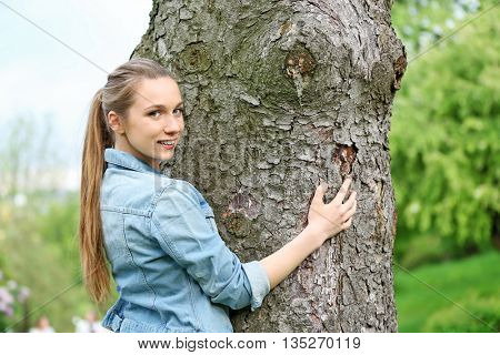 Young beautiful woman hugging tree trunk