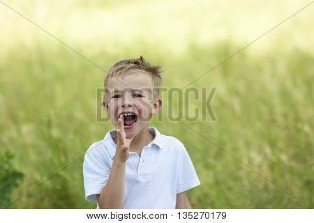 Portrait of young boy shouting loudly on summer day