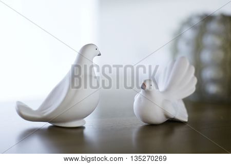 Two bird figures stand on the table