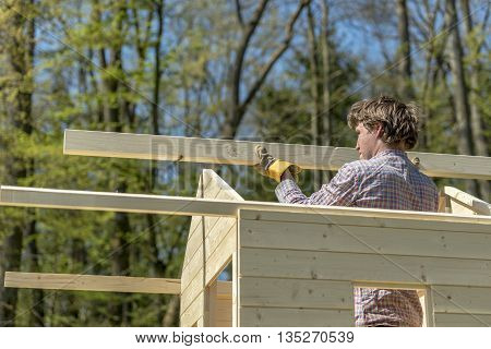 Young man placing the main wooden beam to assemble a roof of a wooden playhouse outside in nature in a DIY concept.