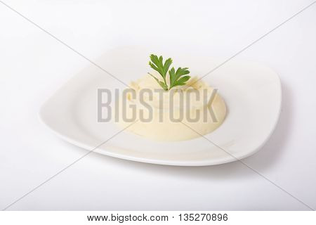 Mashed potato garnish served on a white plate