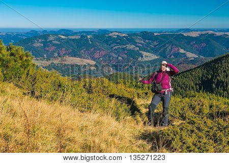 Woman Staying on Grassy Meadow in Mountain Landscape Hiker on Trail Hills with Autumnal Forest and Blue Sky Background