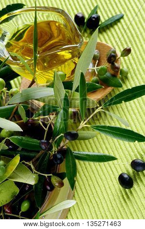Arrangement of Raw Green and Black Olives with Leafs and Olive Oil in Glass Gravy on Wooden Plate closeup on Green Textile background
