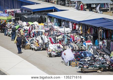 CHISINAU MOLDOVA- 25 JUN 2016: Tourists and locals looking at the stalls at Chisinau flea market in Moldova. At the flea market one can find second hand clothes and shoes souvenirs and paintings