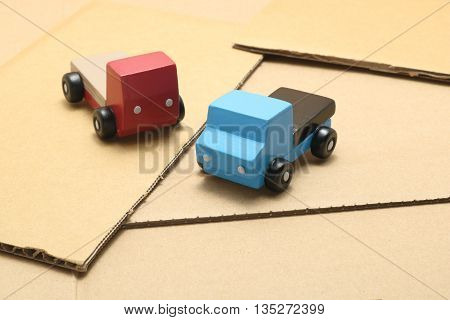 Toy car trucks on cardboard. logistics image.