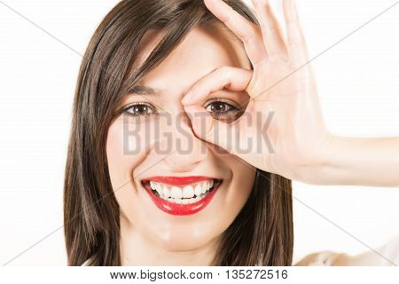Close up portrait of happy smiling beautiful young woman showing okay gesture, studio shot on white background