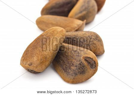 Unpeeled cedar nuts on white background. Siberian cedar seeds, Pinus sibirica.