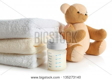 Baby bottle with milk, pile of soft towels and teddy bear isolated on white