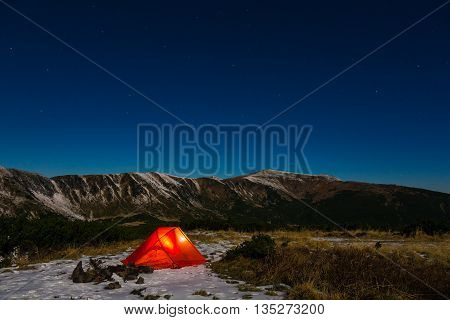 Night mountain landscape with illuminated tent Silhouettes of snowy mountain peaks and edges night sky with many stars and milky way on background