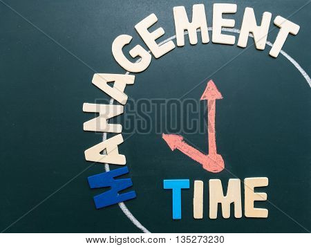 Time Management wording and hand writing clock at 10 am on blackboard - business concept of time management