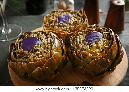 Tasty baked artichokes on round wooden board, close up
