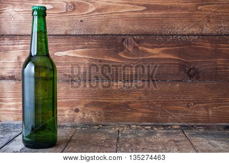 Bottle Of Cold Beer With Foam On Wood Table With Wood Background,text Space