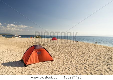 tents on beach of white sandunder blue sky with sweeming people and philippine boat