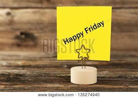 Yellow note paper on a holder on brown wooden background, happy friday