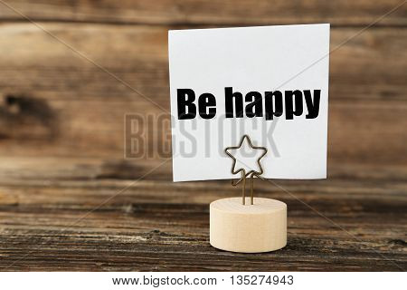 White note paper on a holder on brown wooden background, be happy