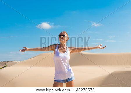 MUI NE, VIETNAM - April 28, 2014 - Beautiful young woman wearing sunglasses in desert sand dunes