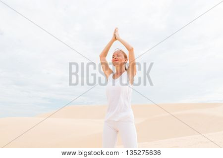 MUI NE, VIETNAM - April 30, 2014 - Young woman practicing yoga in the desert