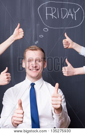Happy young man holding his thumbs up around him hands with thumbs up friday written on a blackboard
