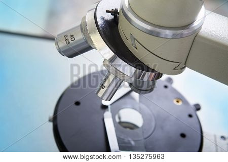 Professional microscope close-up with chemist scientific researcher hands using microscope in the laboratory interior.